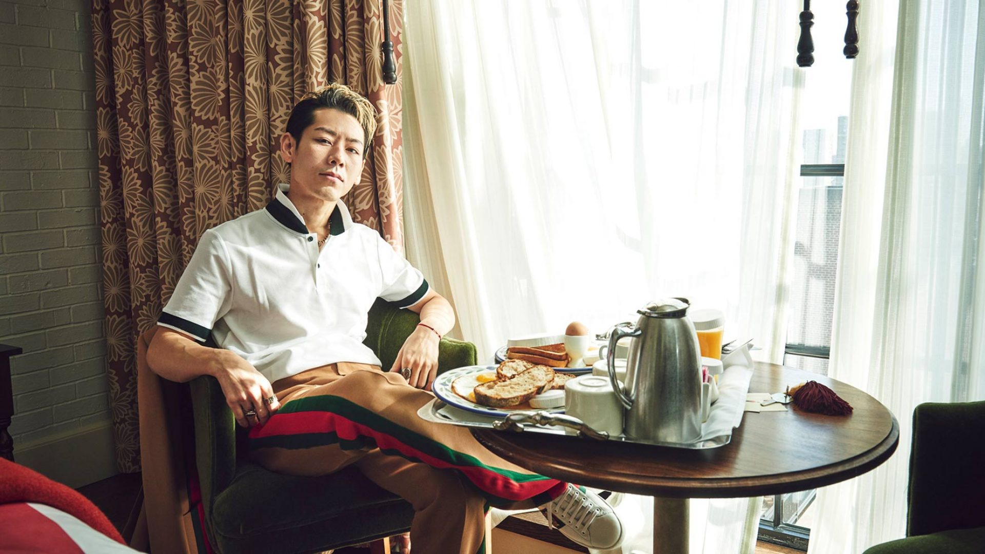 Takeru Kobiyashi sits in a hotel room with room service