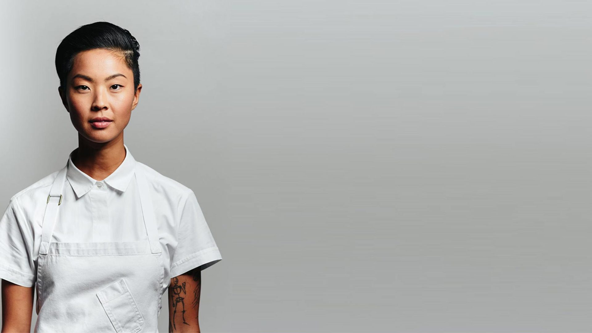 Kristen Kish a Korean chef facing the camera infront of a grey background