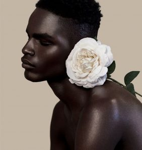 a black man infront of a nude background poses with a flower
