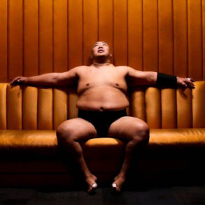 Sumo wrestler Byamba sitting on a couch