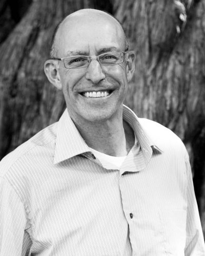 micheal pollan stands infront of a tree wearing a shirt and smiling at the camera in black and white