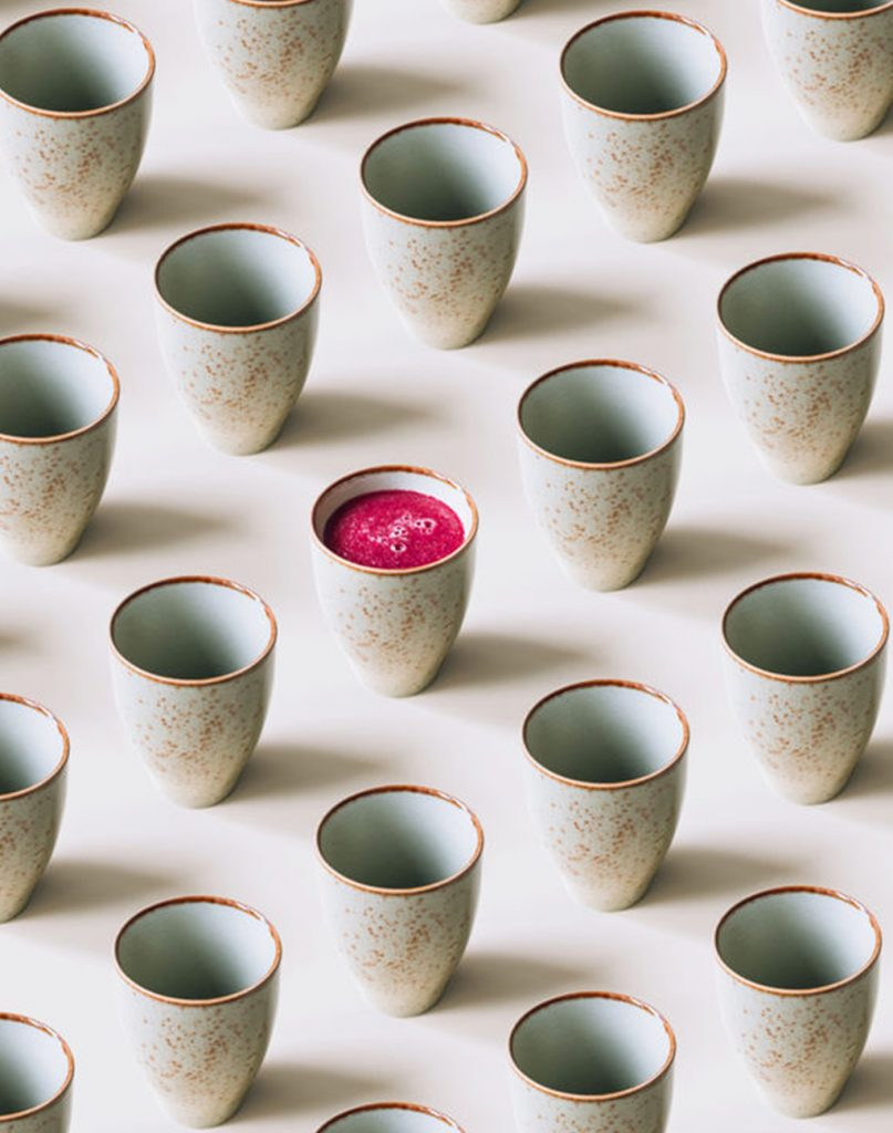 rows of symmetrical white cups one filled with bright pink liquid