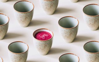 A row of ceramic Japanese inspired mugs with one mug containing pink juice
