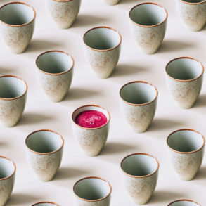 A row of Japanese inspired ceramic mugs with one mug containing pink juice