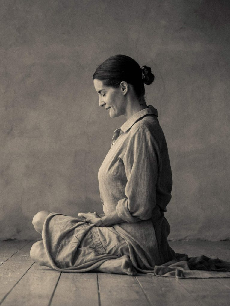 elena brower wears loose linen clothing and sits crossed leg looking peaceful sepia photo