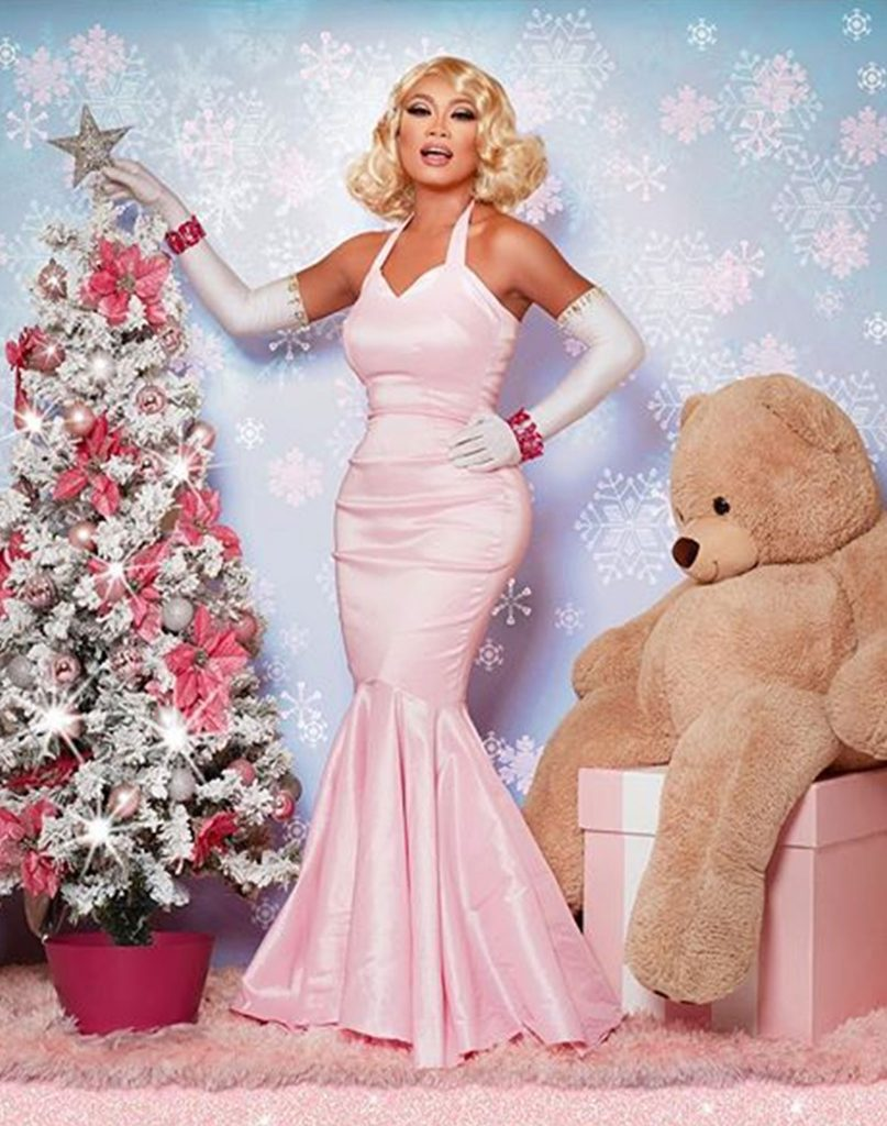 jujubee the drag queen stands infront of a christmas dress wearing a pink dress.