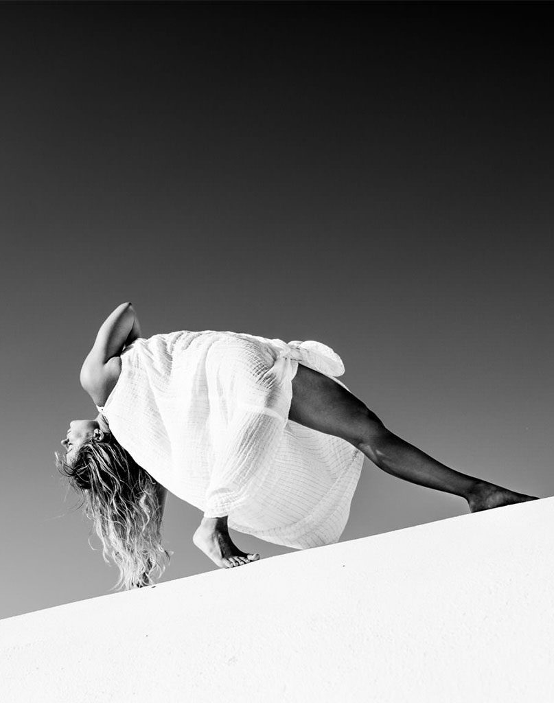 kathryn budig leans backwards in a yoga pose in black and white
