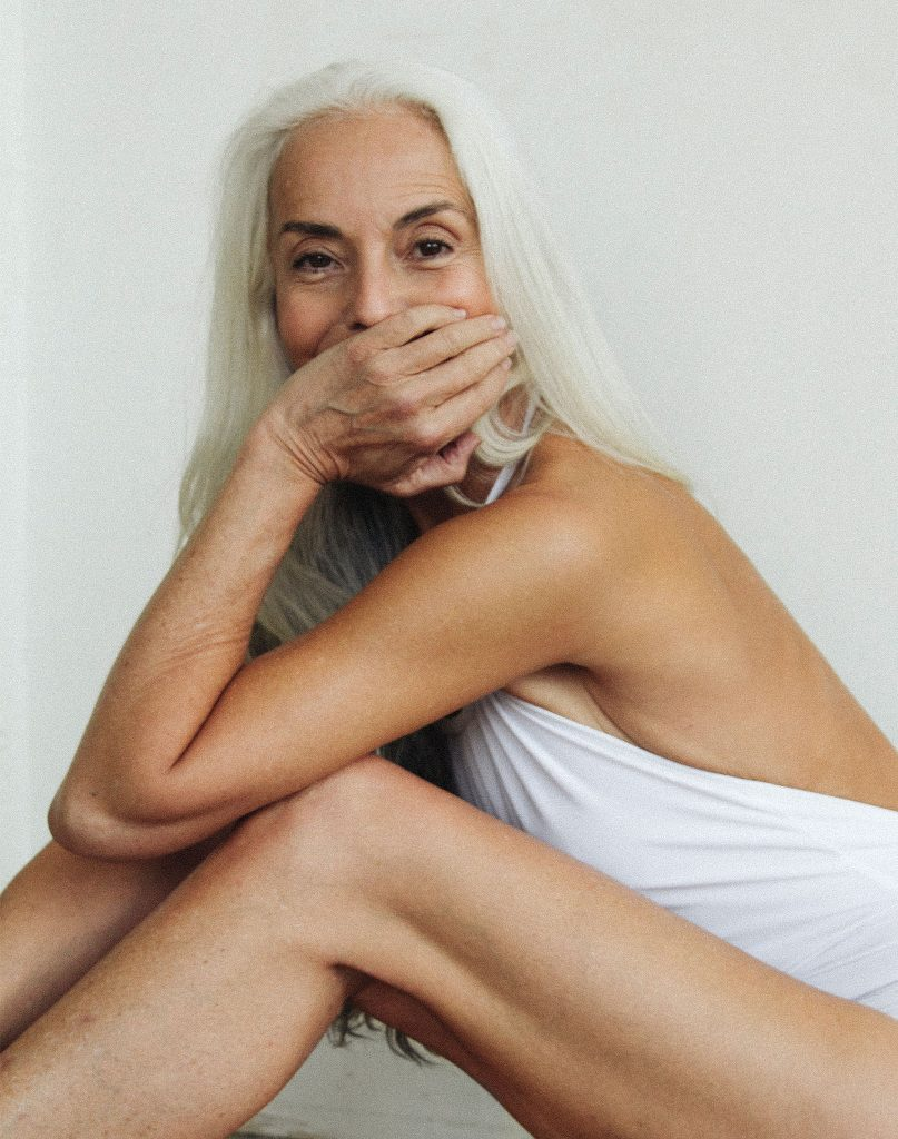 Yazemeenah Rossi a woman in her 70s with long white hair sits in a swimming costume covering her mouth with her hand looking at the camera.