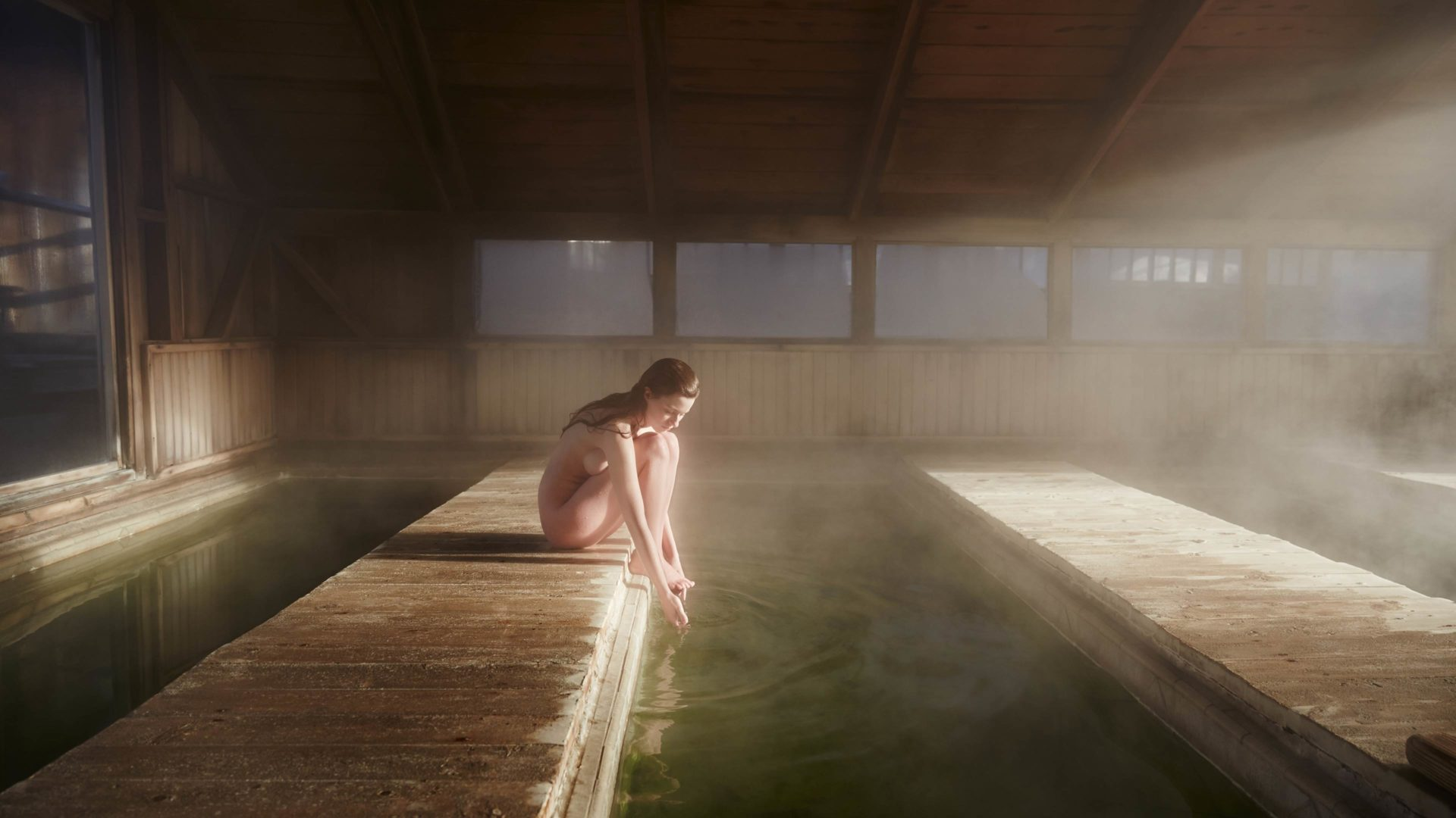 Women sits naked by a green pool, the warm water is steaming