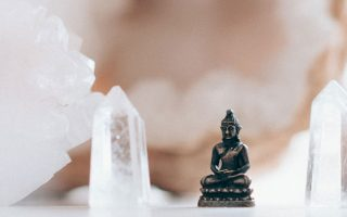Small buddha figurine framed by crystals