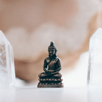 Small buddha figurine framed by crystals