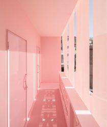 A pastel pink corridor with streaks of daylight coming through