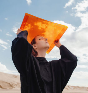 Girl holds up orange sheet against a blue sky