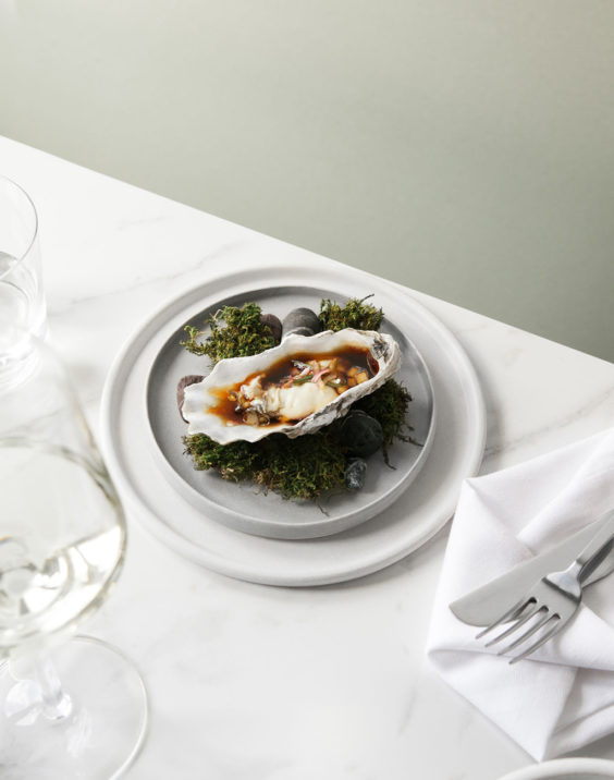 an oyster sitting on a plate on top of grass