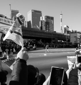 black and white image of flags waving as a long distance runner