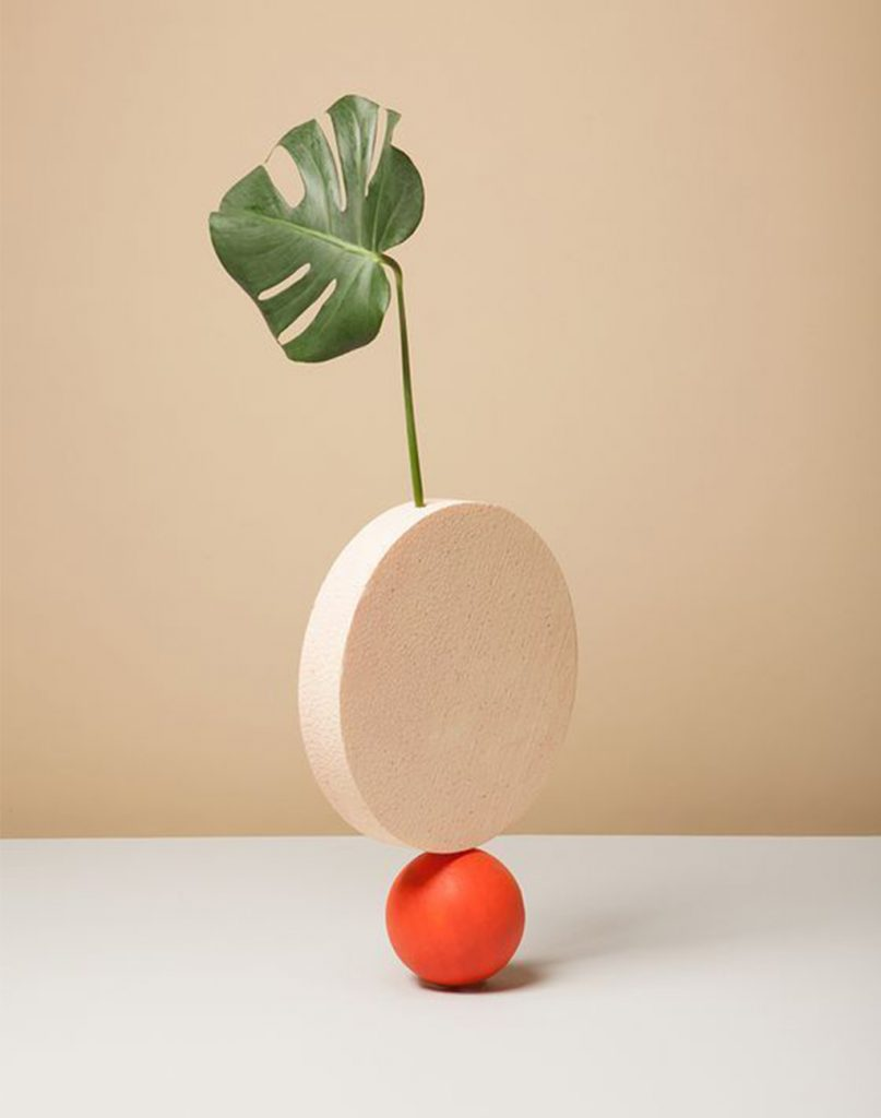a circular nude stone sits ontop of a small orange stone with a leaf