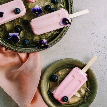A still life of pink ice cream lollipops in green bowls decorated with flowers