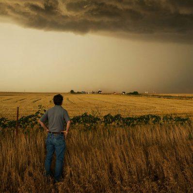 Storm chaser Tim Samaras looks across a field at dark storm clouds
