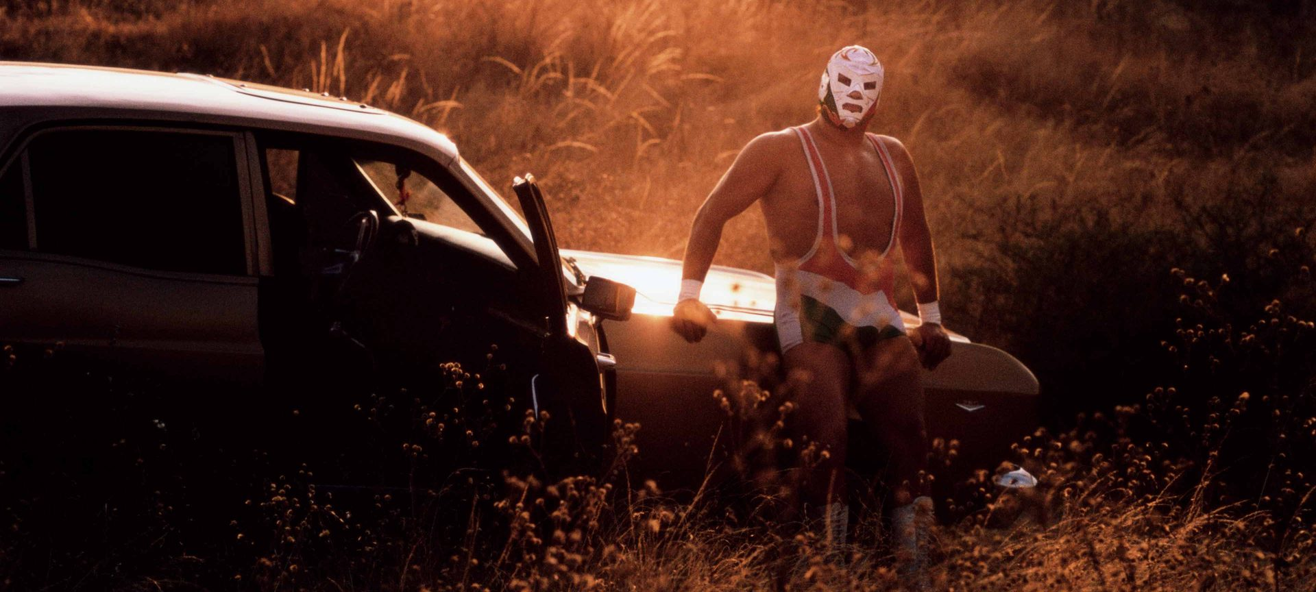 Mexican luchador Dr Wagner Jr poses by his car in front of a sunset