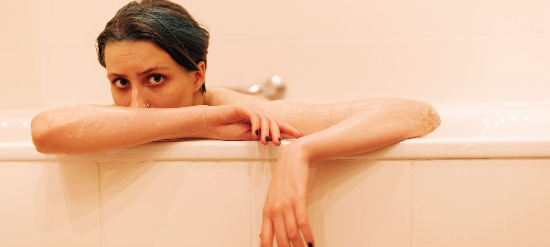 A female model sits in a pink bathtub looking out