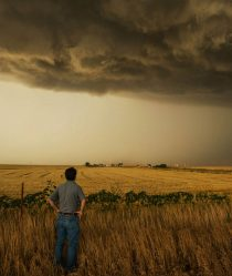 Storm chaser Tim Samaras looks across a field at dark storm clouds