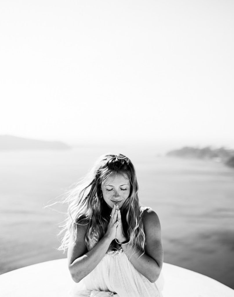 kathyrn budig sits infront of the ocean with hands clasped in a yoga pose