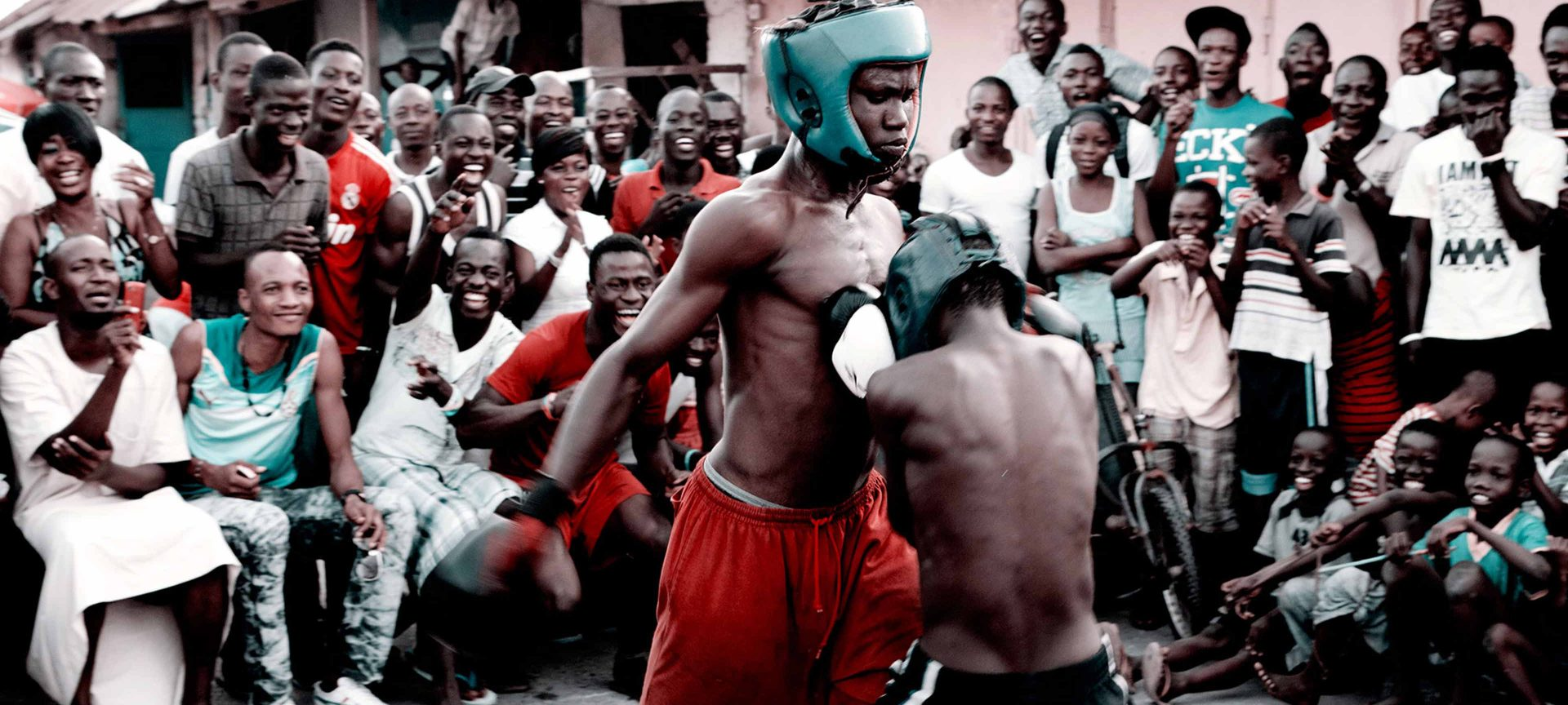 Two young Bukom boxers spar in a ring, cheered on by a crowd