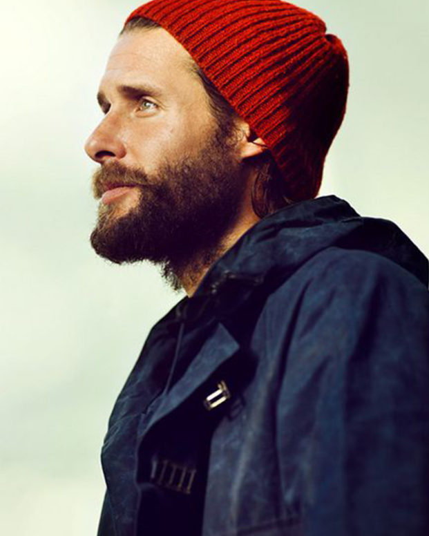 david de rothschild wears a red beanie and outdoor coat infront of a pale green background