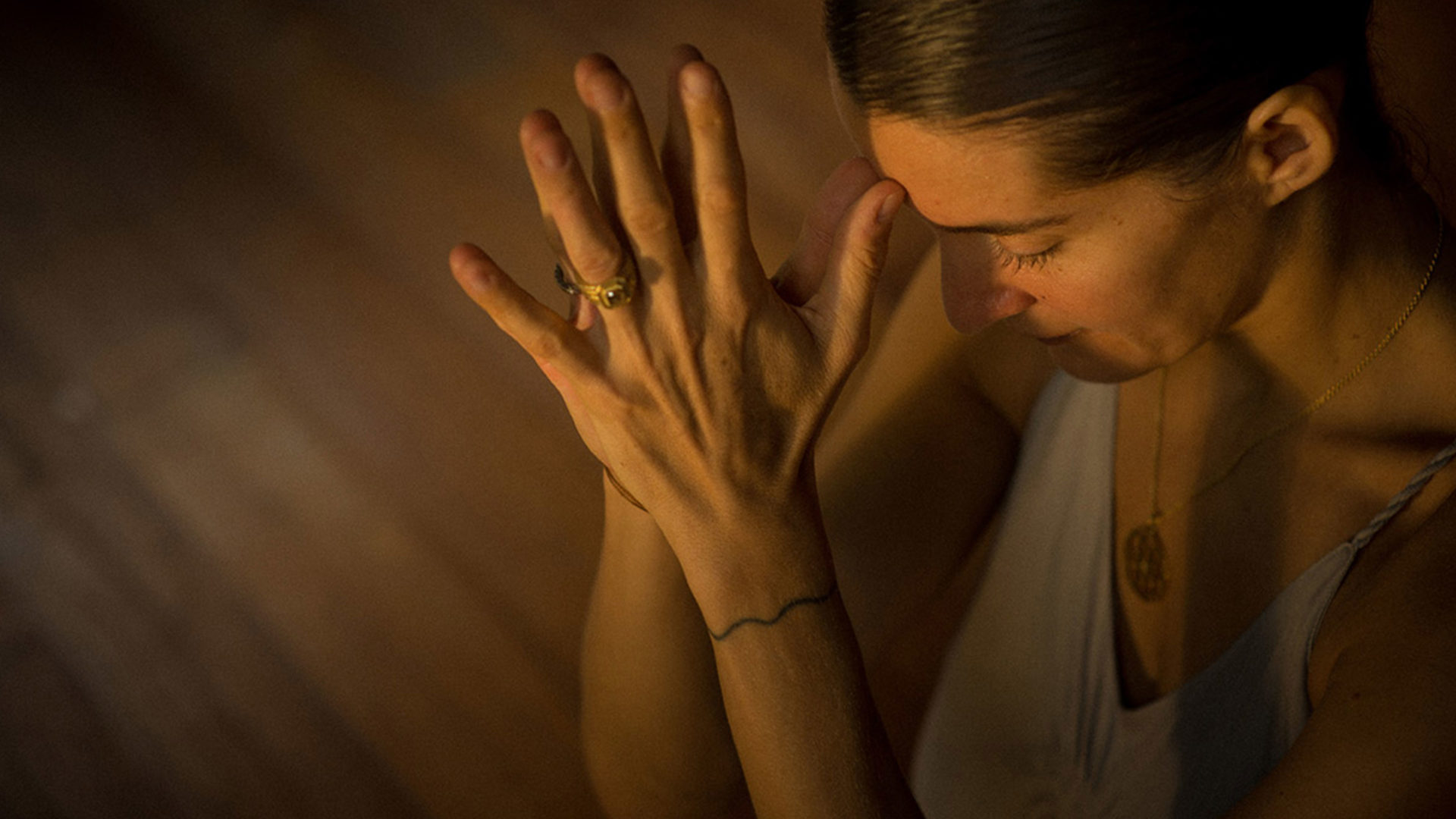 elena brower clasps hands in a yoga pose and holds them to her forehead