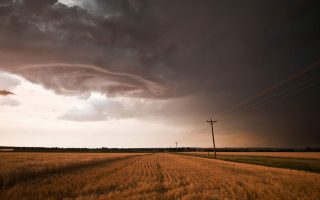 a storm brews over a american corn field