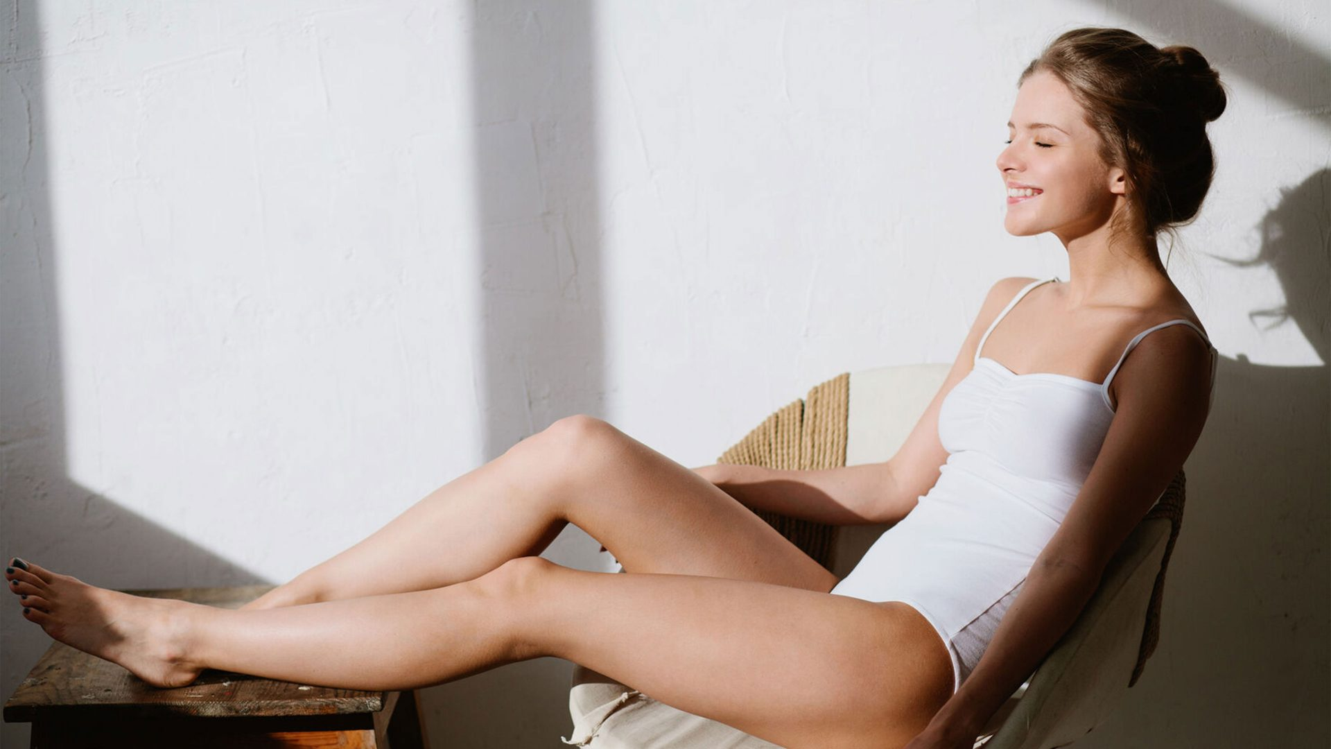 A girl wearing a white leotard sits in a chair and smiles facing sunlight