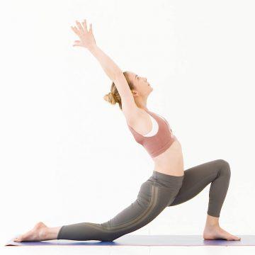 Model wears pink sports bra and green leggings in yoga pose