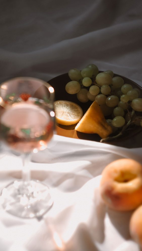 A glass of rose wine arranged with plates of fruit