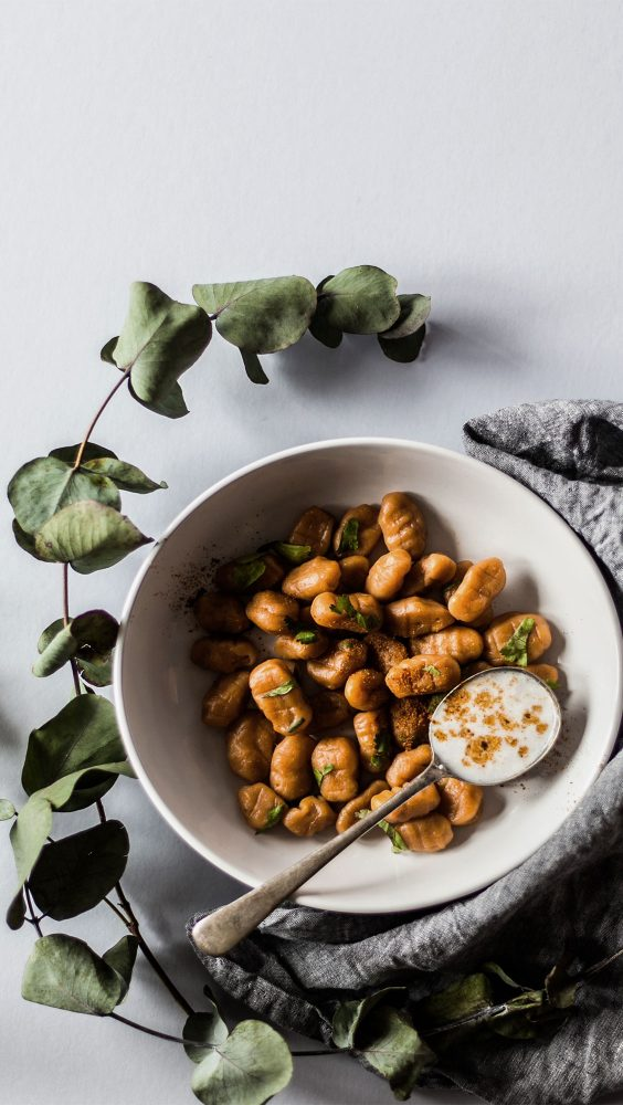 A bowl of gnocchi presented with a branch of leaves and grey linen cloth