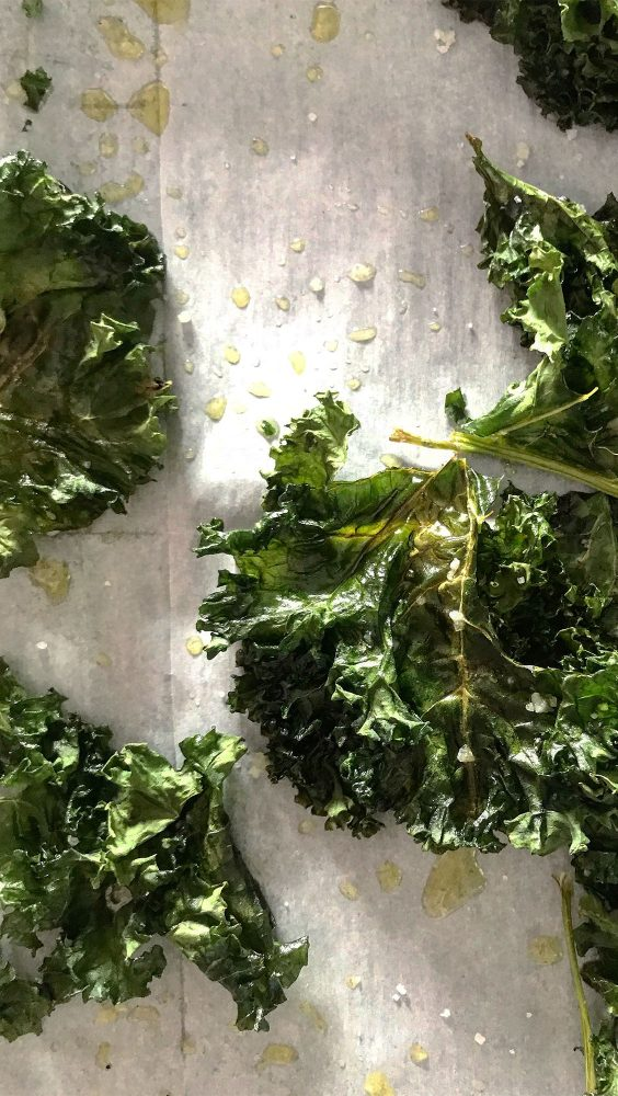 Leaves of kale on a wooden board with sprinkles of salt and oil