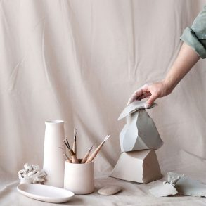 A hand arranges ceramic sculptures alongside artist tools against a pastel pink studio backdrop
