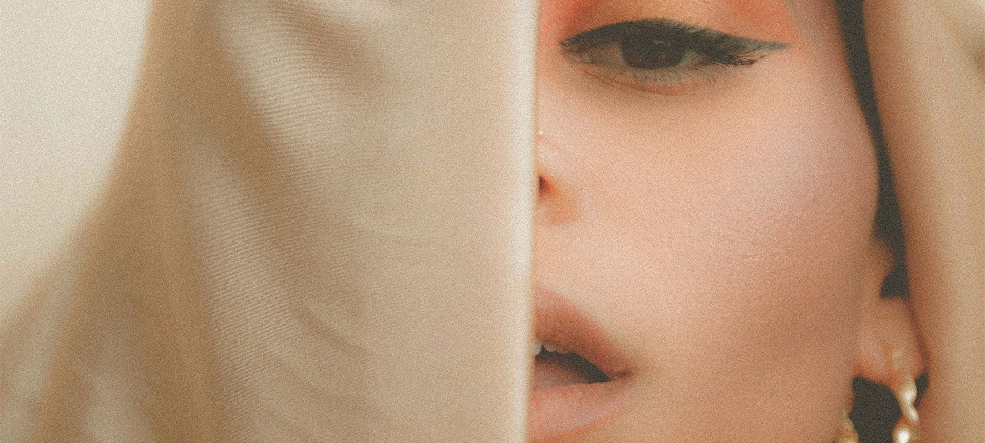 A young woman's face partially obscured by a veil