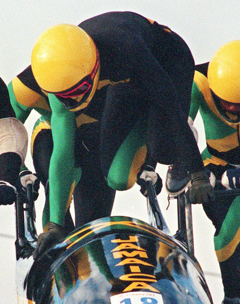 The first Jamaican bobsled team jumps into a bobsled