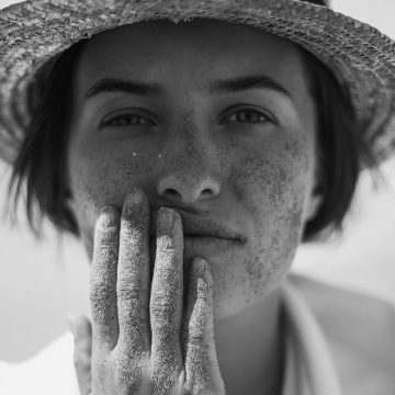 Black and white photograph of model wearing a sun hat holding her face
