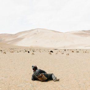 Young Kashmirin boy lies in a dessert looking at mountains