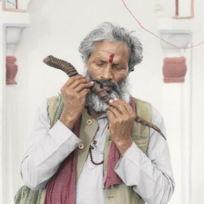 An old Indian man plays on a wooden flute