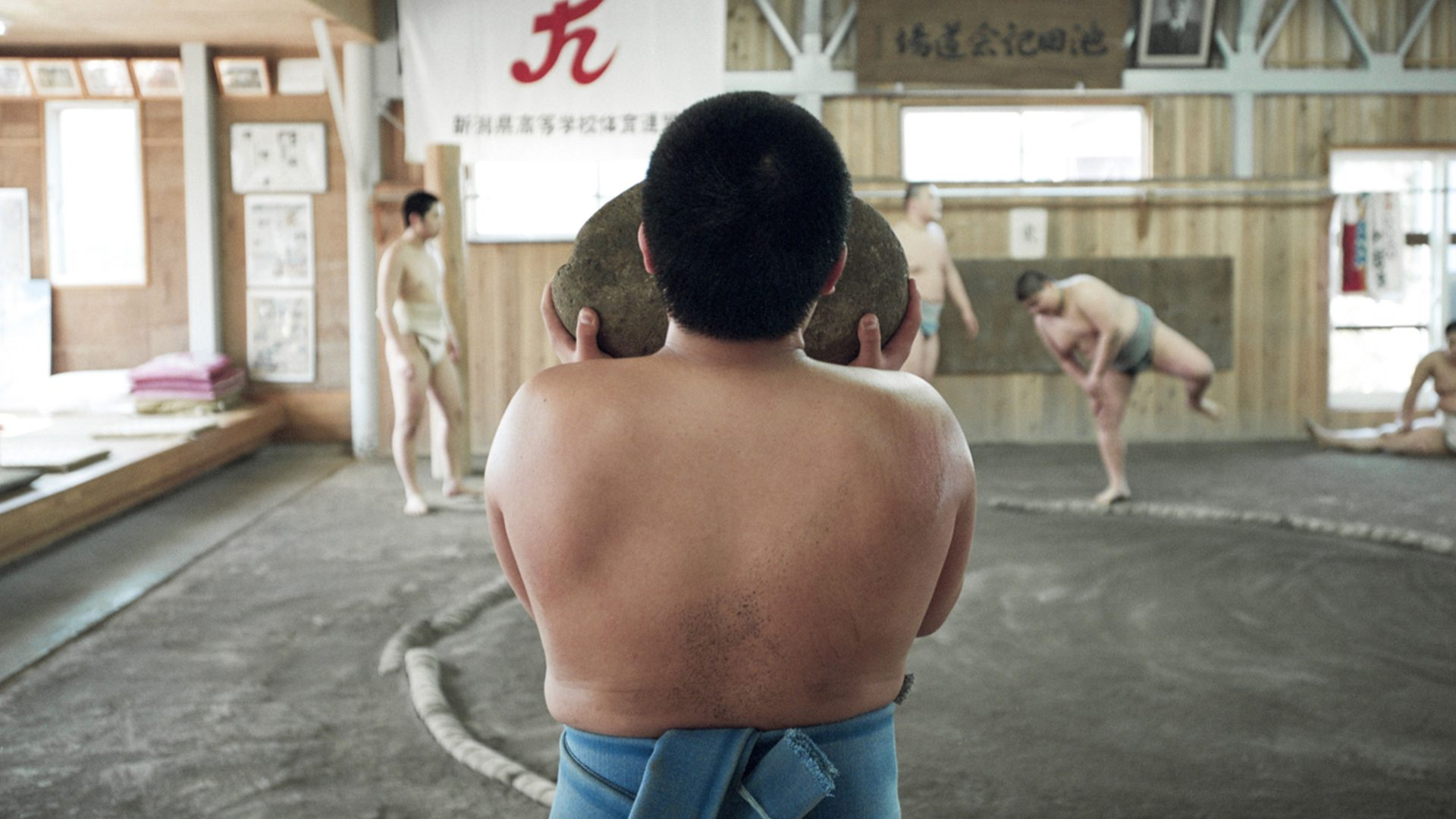 A young Japanese sumo carries a heavy weighted rock