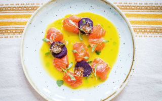 Trout and toradito ceviche in a bowl of tiger's milk dressed with sprigs of green